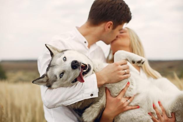 Пара в осеннем поле играет с собакой