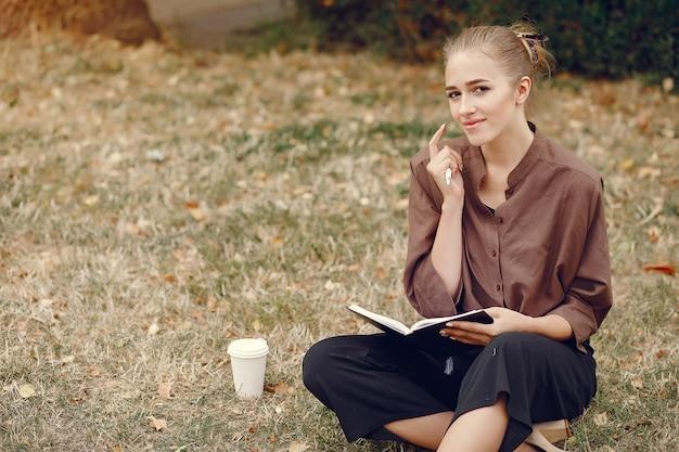 Симпатичная студентка работает в парке и пользуется тетрадью