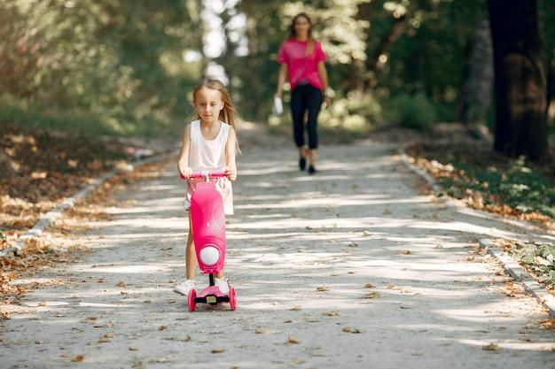 Мать с дочерью, играя в парке летом