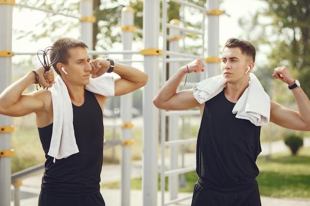 Красивые мужчины в спортивной одежде, стоя в парке