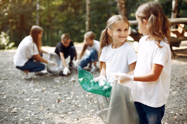 Дети собирают мусор в мешки для мусора в парке