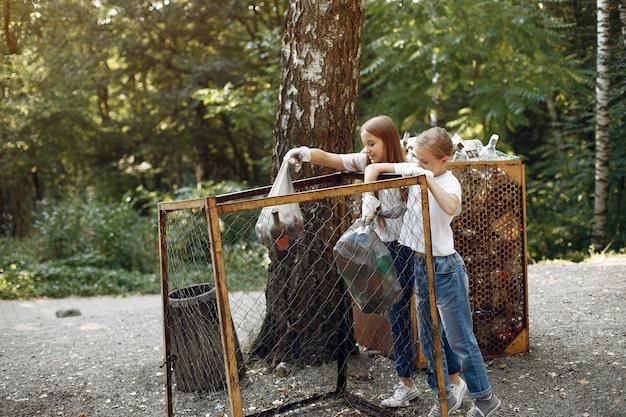 子供たちは公園でゴミ袋にゴミを収集します