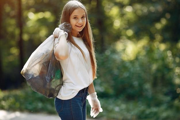 女の子は公園でゴミ袋にゴミを収集します