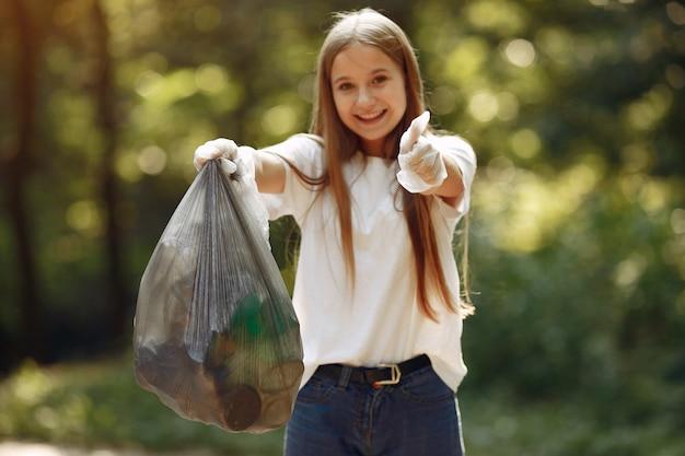 Девушка собирает мусор в мешки для мусора в парке