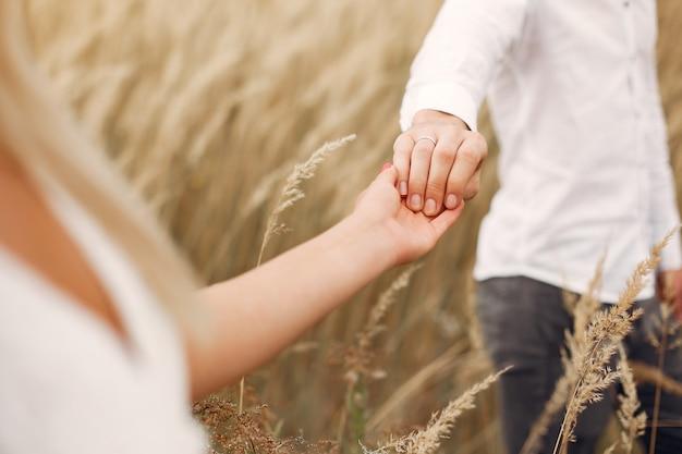 美しいカップルが秋のフィールドで時間を過ごす