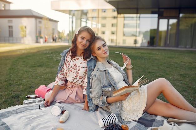 Девушки сидят на одеяле в летнем парке