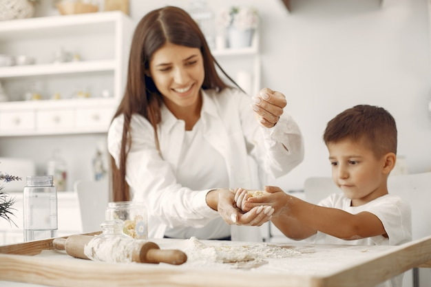 Семья сидит на кухне и готовит тесто для печенья