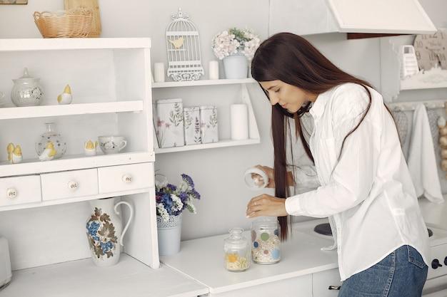 Женщина в белой рубашке стоя в кухне с овсянкой