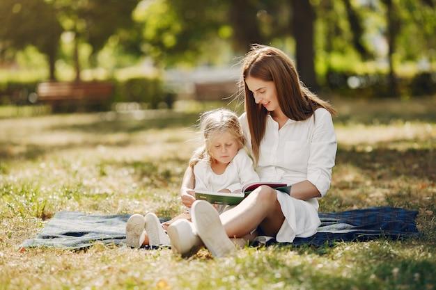 Мама с маленькой дочкой сидят на пледе и читают книгу