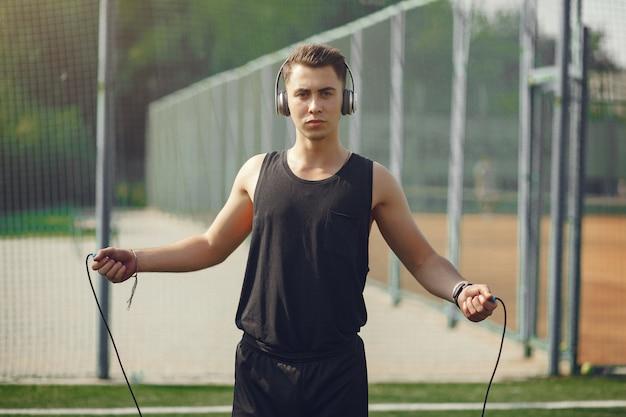 Красивый мужчина, обучение в летнем парке со скакалкой