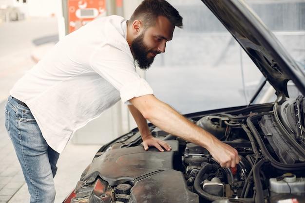 ハンサムな男は彼の車のエンジンをチェックします