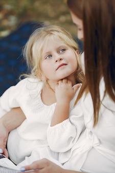 格子縞の上に座って本を読む小さな娘を持つ母
