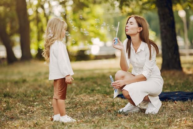 夏の公園で遊ぶ幼い娘を持つ母