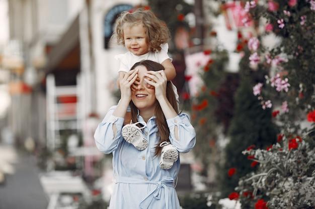 Мать с дочерью играет в летнем городе
