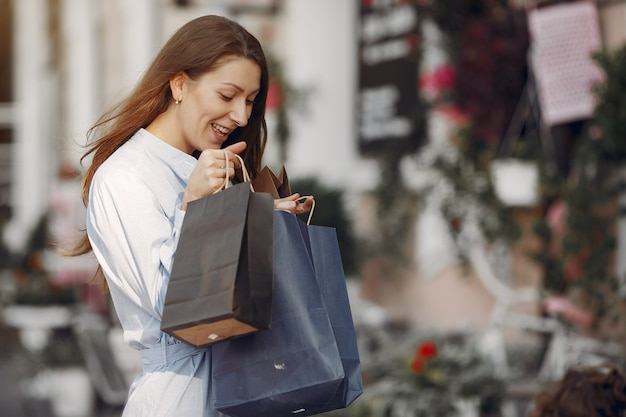 都市の買い物袋と青いドレスの女