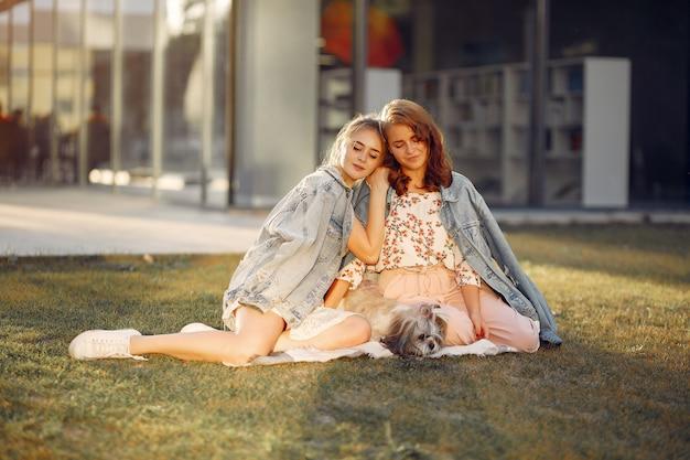 Две девушки сидят в парке с маленькой собачкой
