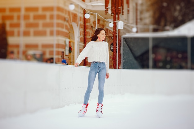Милая и красивая девушка в белом свитере в зимнем городе