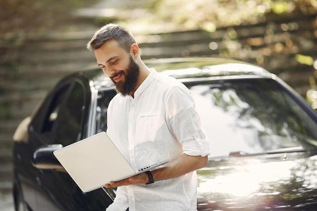 車の近くに立って、ラップトップを使用してスタイリッシュなビジネスマン