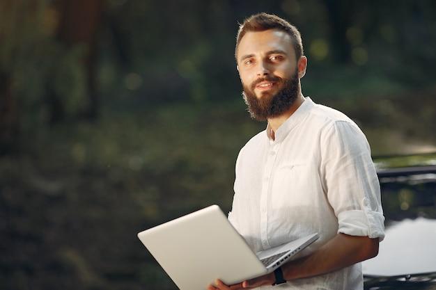Стильный бизнесмен стоит возле машины и пользуется ноутбуком