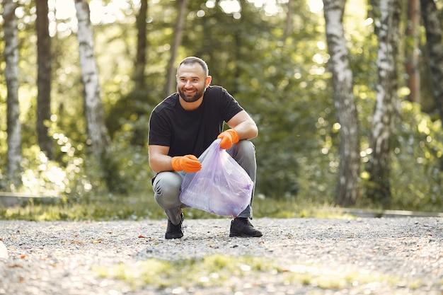 男は公園でゴミ袋にゴミを収集します