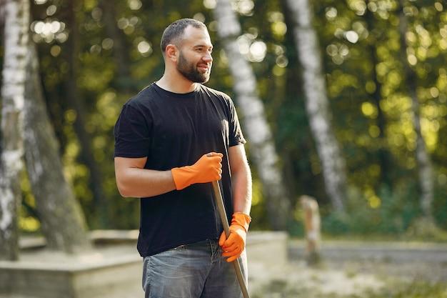 男は葉を収集し、公園をきれいに