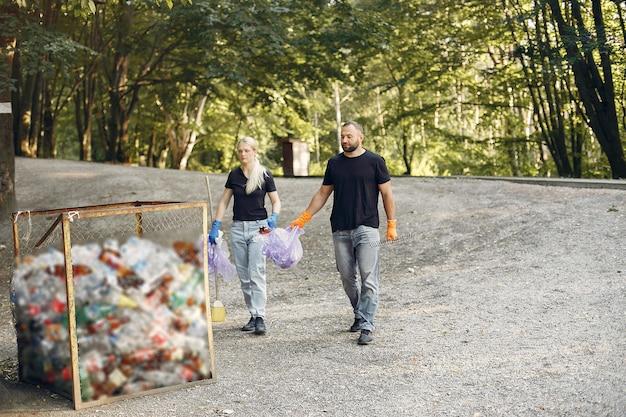 カップルは公園でゴミ袋にゴミを収集します