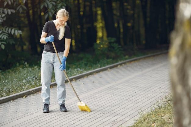 女性が葉を集めて公園を掃除する