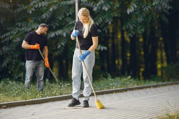 カップルが葉を集めて公園を掃除する