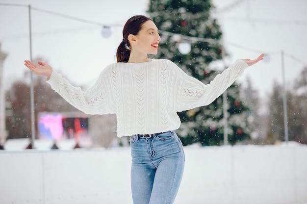 冬の公園に立っている白いセーターの少女