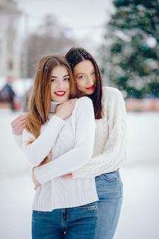 Молодая девушка в белом свитере стоит в зимнем парке