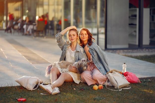 Две девушки в парке с маленькой собачкой