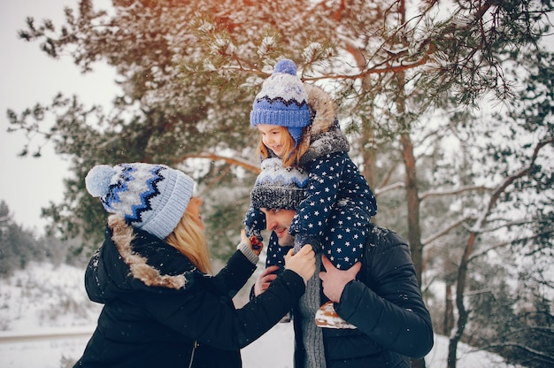 冬の公園で遊んでいる両親と小さな女の子