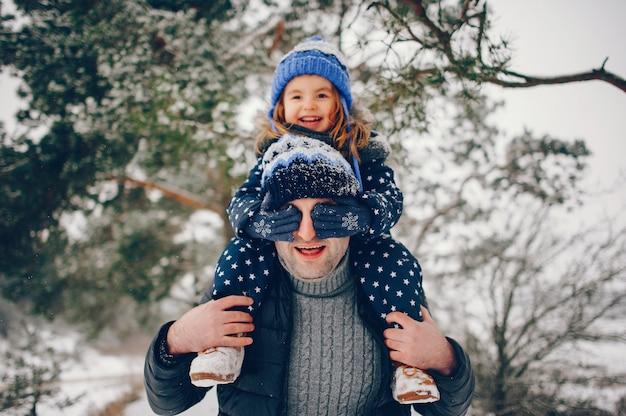 Маленькая девочка с отцом, играя в зимнем парке