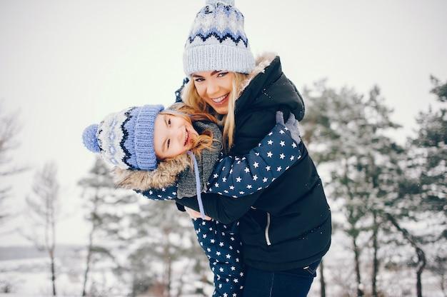 Маленькая девочка с матерью, играя в зимнем парке