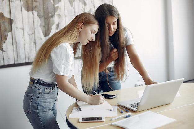 Две девушки в белых футболках работают в офисе