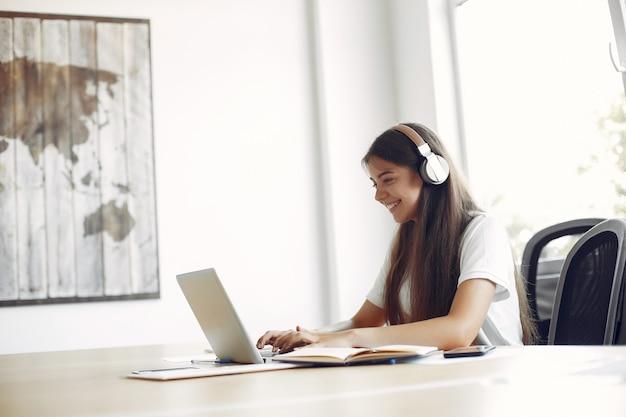 Молодой студент сидит за столом и пользуется ноутбуком