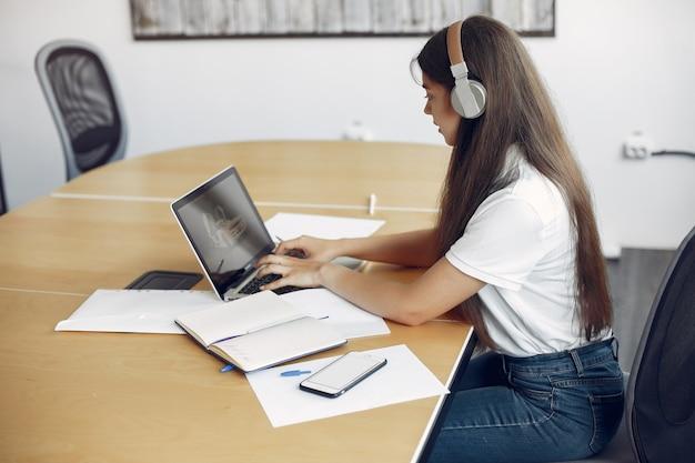 若い学生がテーブルに座ってラップトップを使用