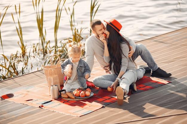 Семья с маленькой дочерью сидит возле воды в осеннем парке