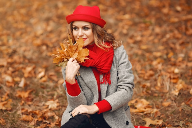 Красивая женщина сидит в осеннем парке