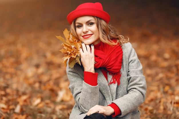 秋の公園に座っている美しい女性