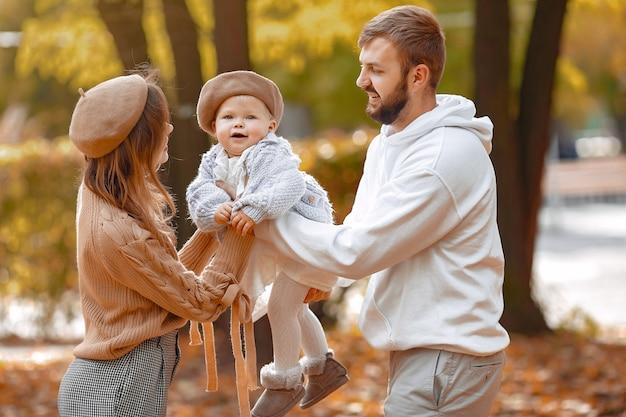 Семья с маленькой дочкой в осеннем парке