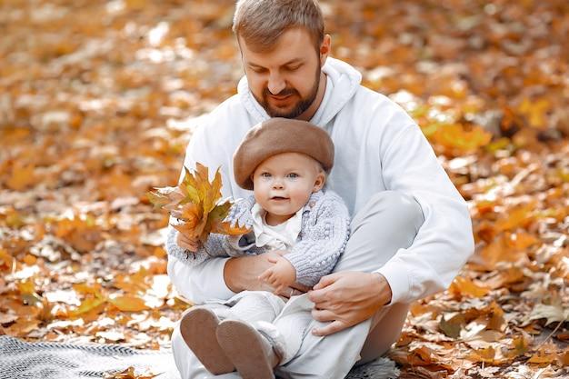 Красивый отец в сером свитере играет с маленькой дочкой в осеннем парке