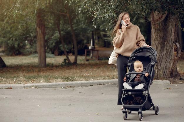 キャリッジと秋の公園を歩く若い母親