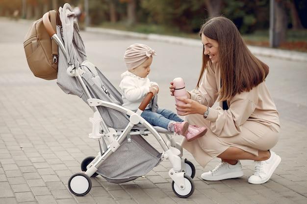 Молодая мама гуляет в осеннем парке с коляской