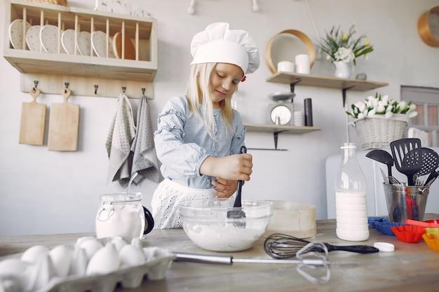 白いシェフの帽子の少女がクッキーの生地を調理します。