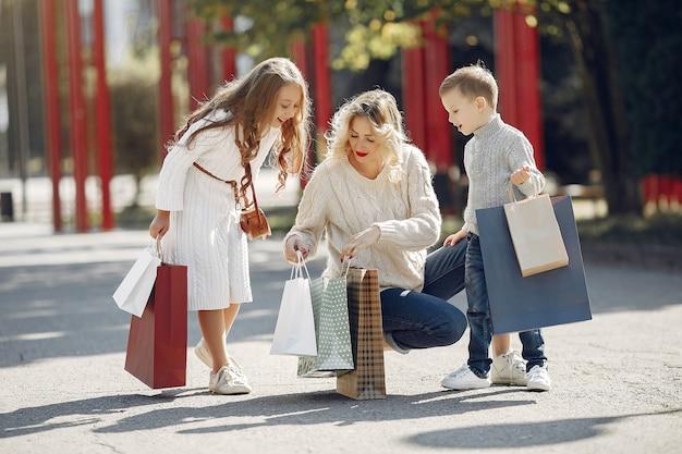 街で買い物袋を持つ子供を持つ母