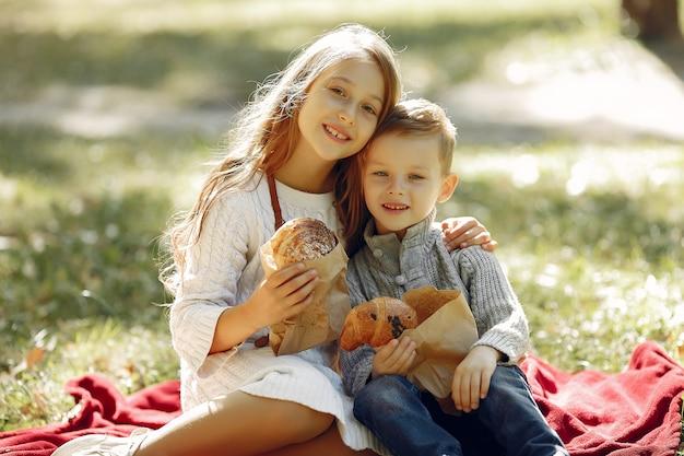 Симпатичные маленькие дети, сидя в парке с хлебом