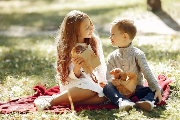 パンと公園に座っているかわいい小さな子供たち