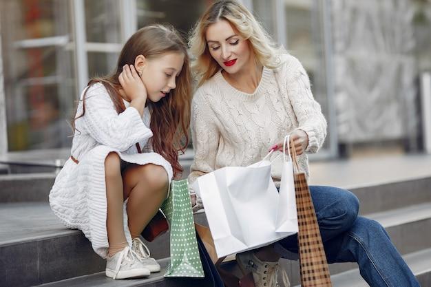 街で買い物袋を持つ娘を持つ母