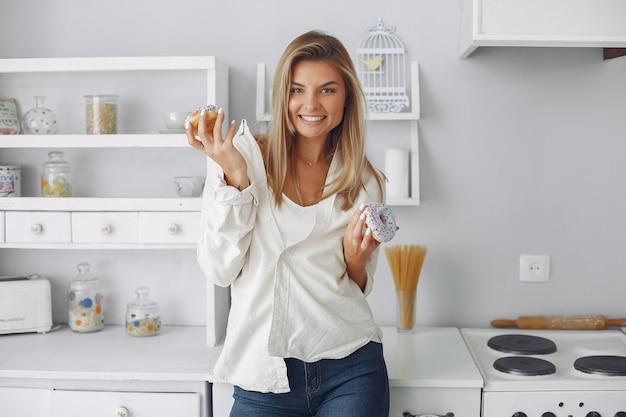 ドーナツとキッチンに立っている美しい女性